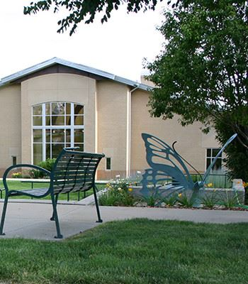 Sump Memorial Library garden with a bench and butterfly statue