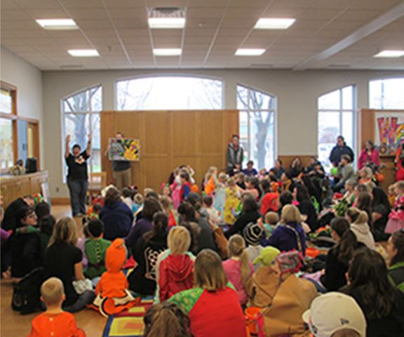 Children and adults gathered around a storyteller in the library